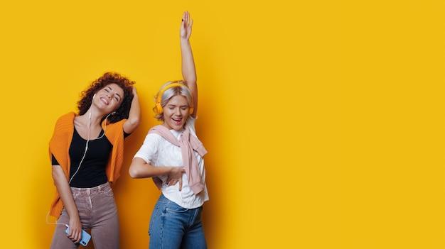 Juichende zus met krullend haar luistert naar muziek op een gele muur met vrije ruimte