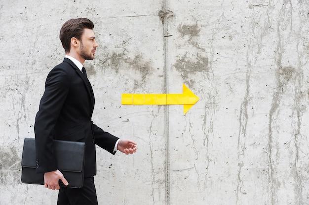 Juiste richting. knappe jonge man in formalwear met aktetas terwijl hij voor de betonnen muur loopt