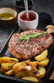 Juisy new york strip steak met rozemarijn, knoflook en aardappel op een koekenpan.