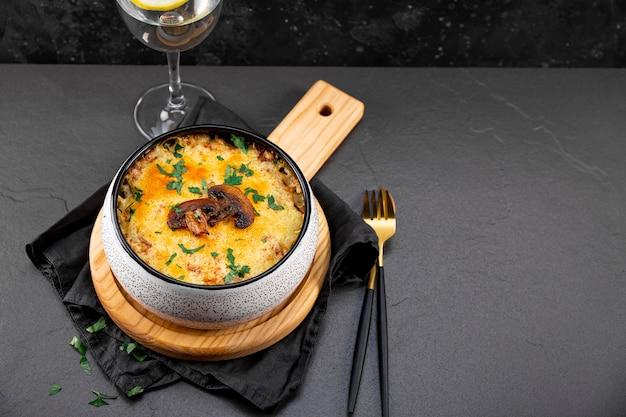 Julienne met aardappelen en champignons in een ovenschaal op een donkere achtergrond