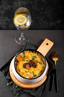 Julienne met aardappelen en champignons in een ovenschaal op een donkere tafel