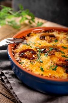 Julienne met aardappelen en champignons in een ovenschaal op een houten achtergrond close-up verticale foto