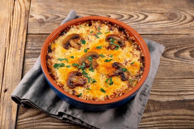 Julienne met aardappelen en champignons in een ovenschaal op een houten ondergrond