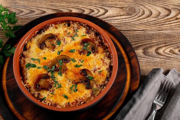 Julienne met aardappelen en champignons in een ovenschaal op een houten tafel