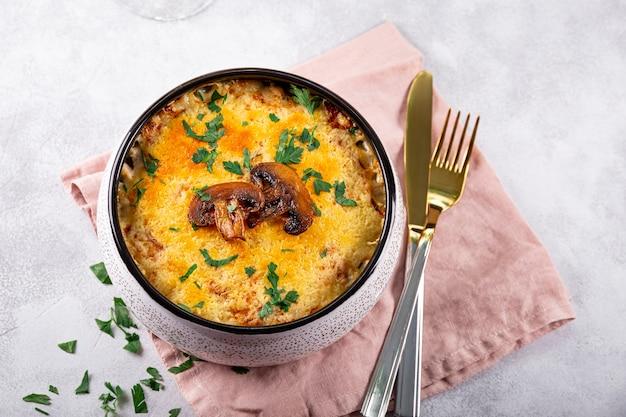 Julienne met aardappelen en champignons in een ovenschaal op een lichte achtergrond traditionele franse schotel
