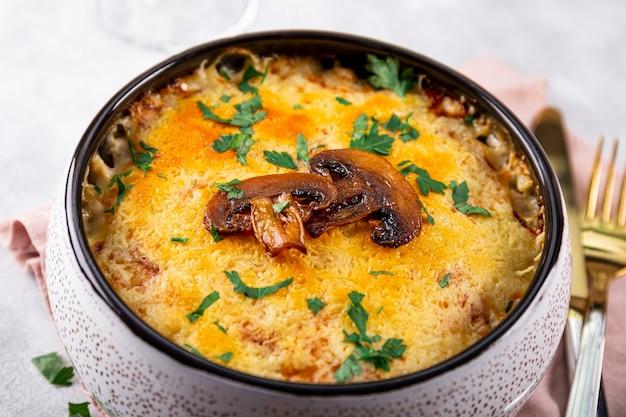 Julienne met aardappelen en champignons in een ovenschaal op een lichte achtergrond