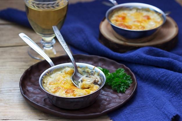 Julienne met champignons en bechamelsaus met kaas, geserveerd met witte wijn. rustieke stijl.
