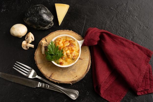 Julienne met kaas, champignons, kip en peterselie. een warme schotel met gebakken kaaskorst op een houten standaard en op een zwarte tafel. bovenaanzicht.