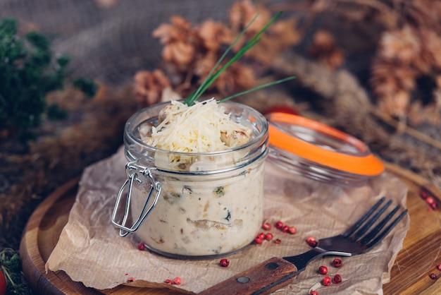 Julienne met kip en champignons in een glazen serveerschaal bestrooid met parmezaanse kaas.
