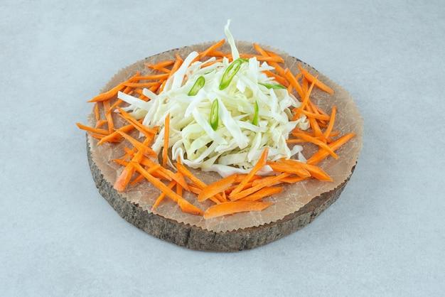 Julienned diverse groenten op houten stuk.