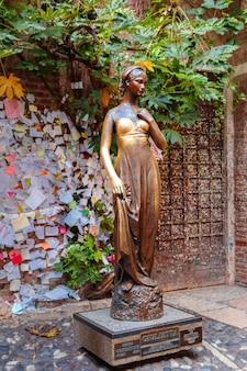Juliet-standbeeld en muur met liefdesnota's in verona, italië