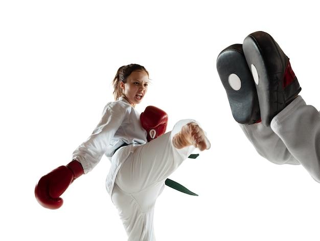 Junior in kimono die hand-tot-hand-gevechten oefent met coach