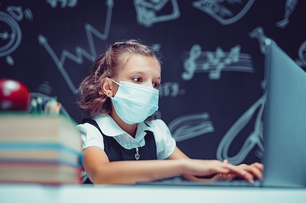 Junior student met medisch masker online virtuele taalles op laptop