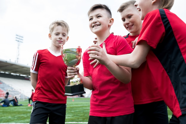 Junior voetbalteam holding cup