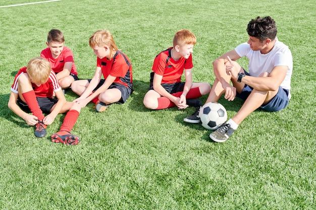 Junior voetbalteam rusten in zonlicht