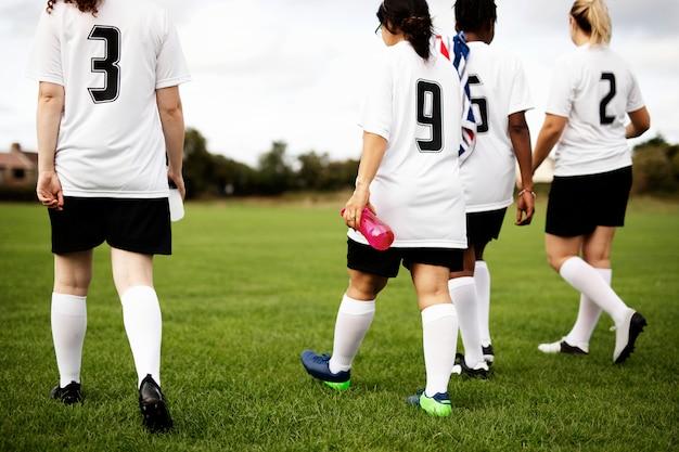 Junior vrouwelijke voetballers lopen op een veld