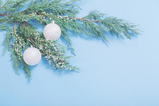 Juniper takken en witte ballen op blauwe achtergrond