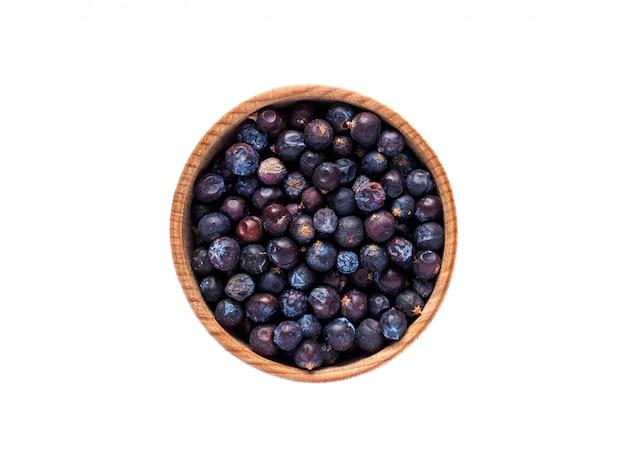 Juniperusfruit in houten kop op witte lijst