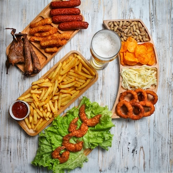 Junk food producten met bier, kaas, barbecue, pistache in houten platen