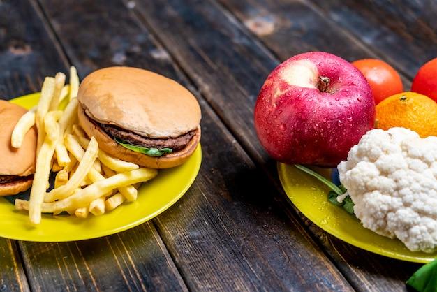 Junkfood of gezonde groenten en fruit op donkere houten tafel geïsoleerd b
