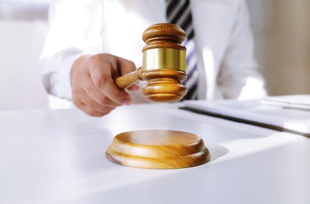 Juridisch adviseur legt de cliënt een ondertekend contract met voorzittershamer en juridisch recht voor. rechtvaardigheid en advocaat concept.