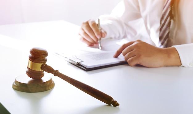 Juridisch adviseur legt de cliënt een ondertekend contract met voorzittershamer voor