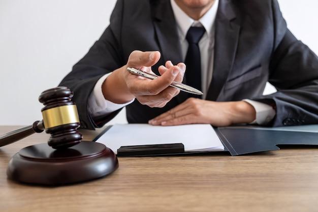 Juridisch recht, advies en rechtvaardigheidsconcept, adviseur-advocaat of notaris die aan documenten en rapport van de belangrijke zaak werkt en houten hamer, koperen schaal op tafel in de rechtszaal