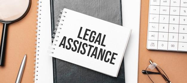 Juridische bijstand op kladblok en diverse zakelijke papieren op bruin