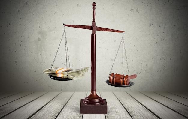 Juridische weegschaal met geld en hamer