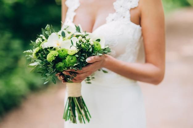 Jurk met diepe halslijn. bruid houdt een bruiloft boeket. bruiloft boeket met groenen. vrouwelijke vorm. aantrekkelijk meisje met een boeket bloemen