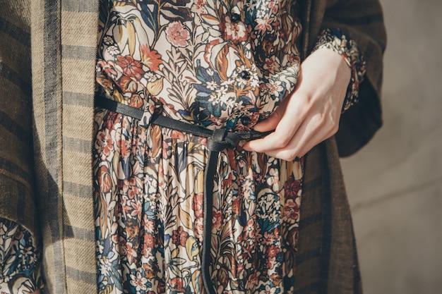 Jurk, pak. vrouwelijke handen, de riem en mouw close-up.