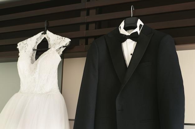 Jurk van het pak van de bruid en bruidegom hangen aan een hanger