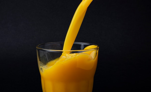 Jus d'orange gieten in glas, geïsoleerd op zwarte achtergrond