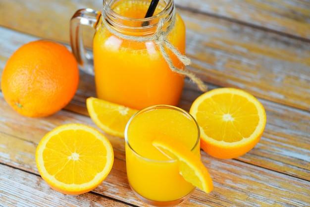 Jus d'orange in de glaskruik en verse oranje fruitplak op houten lijst - het sap van het stillevenglas op houten achtergrond