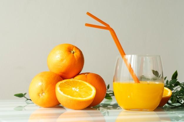 Jus d'orange in een glas omgeven door natuurlijke sinaasappels en enkele groene bladeren met een natuurlijke zon licht witte achtergrond