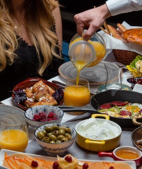 Jus d'orange in glas op tafel zetten met gemengd voedsel.