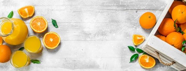 Jus d'orange in glaswaterkruik en verse sinaasappelen op rustieke lijst
