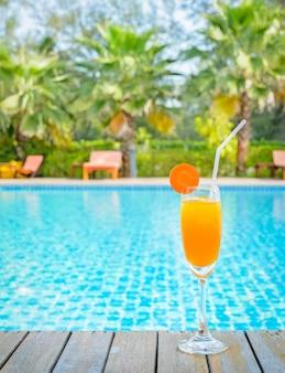 Jus d'orange op houten lijst met de achtergrond van de zwembadmening