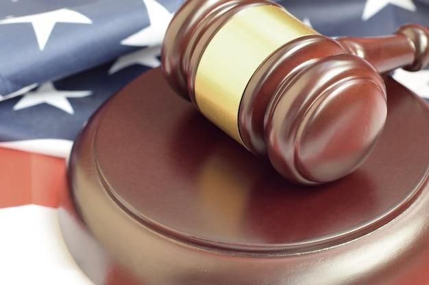 Justitie hamer op de vlag van verenigde staten in een rechtszaal tijdens een gerechtelijk proces