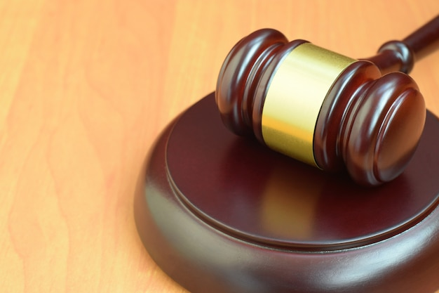 Justitie hamer op houten bureau in een rechtszaal tijdens een gerechtelijk proces. wetsconcept en lege ruimte voor tekst. rechter hamer