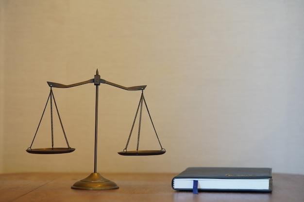 Justitie schaal en wetboek op houten blad in gradiënt pagina