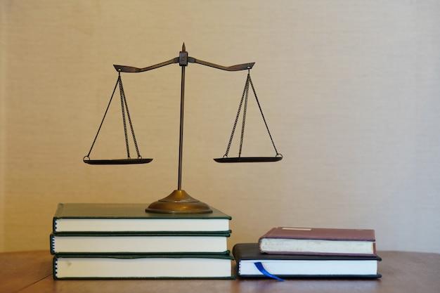 Justitie schaal op stapel boeken in gradiënt witte en bruine achtergrond