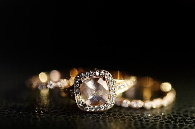 Juwelen schitteren in de gouden trouwringen die op het leer liggen