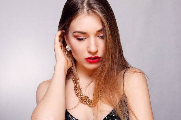 Juwelen, vakantie, luxe en mensenconcept - mooi vrouwelijk gezicht met natuurlijke perfecte huid. gouden vrouwenhuid. gouden oorbellen, ring en ketting. cosmetica, schoonheid en manicure op nagels