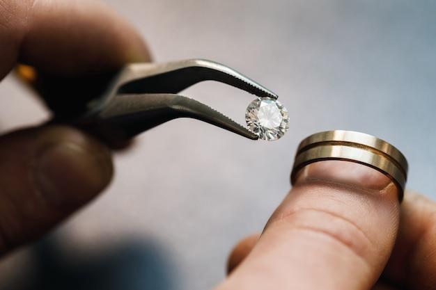 Juwelier probeert een kostbare steen in een gouden blanco voor de toekomst van de ring