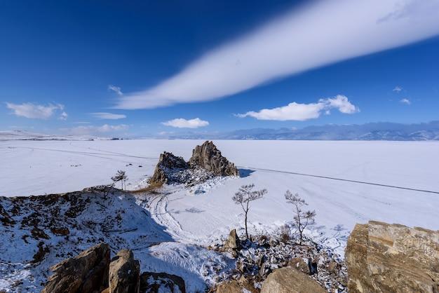 Kaap burhan op shamanka-rots in olkhon-eiland in zonnige maart-dag. lake baikal met prachtige wolken