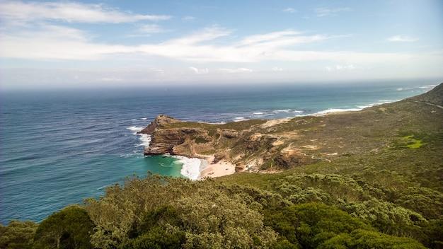 Kaap de goede hoop omgeven door de zee onder het zonlicht overdag in zuid-afrika
