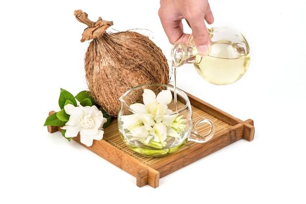 Kaapse jasmijn of gardenia jasminoides bloemen en olie geïsoleerd op een witte achtergrond.