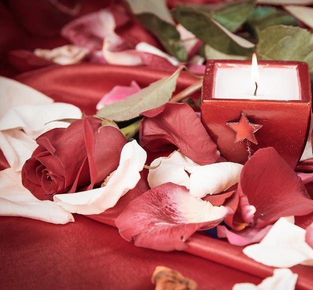 Kaars en een diamanten ring op een achtergrond van rozenblaadjes