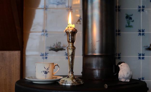 Kaars en een kopje thee op een fornuis op eerste kerstdag
